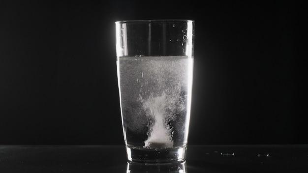 Comprimido branco efervescente em vidro com água na mesa