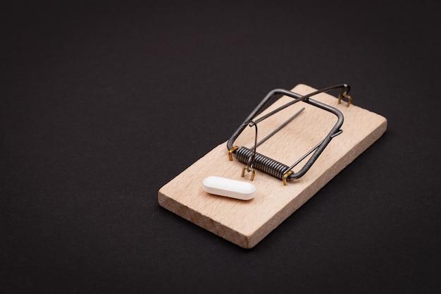 Comprimido branco em ratoeira de madeira, vício farmacêutico