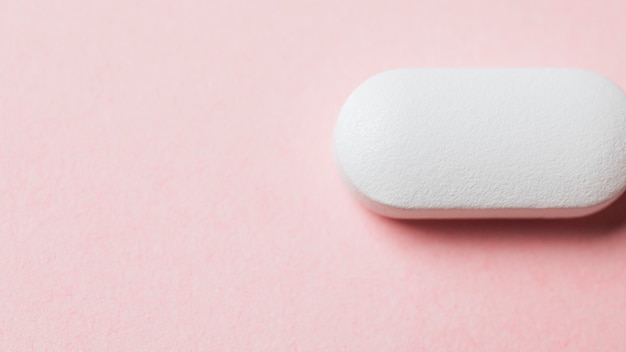 Comprimido branco em uma mesa rosa