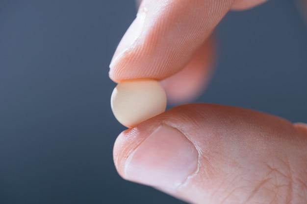 Comprimido branco na mão do médico