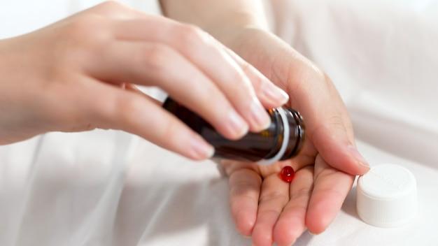 Comprimido caindo da garrafa na mão do paciente feminino.
