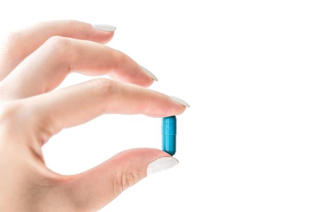 Comprimido, cápsula, medicina na mão fêmea isolada no fundo branco.