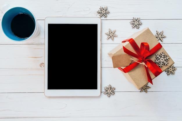 Comprimido com vista superior, copo de café e caixa de presente com flocos de neve no fundo de madeira branca para o natal e o ano novo.