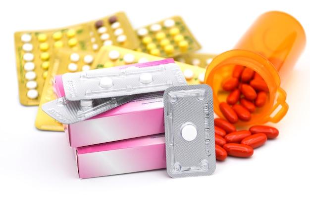Comprimido contraceptivo oral, comprimido de emergência e comprimido de vitamina em fundo branco.