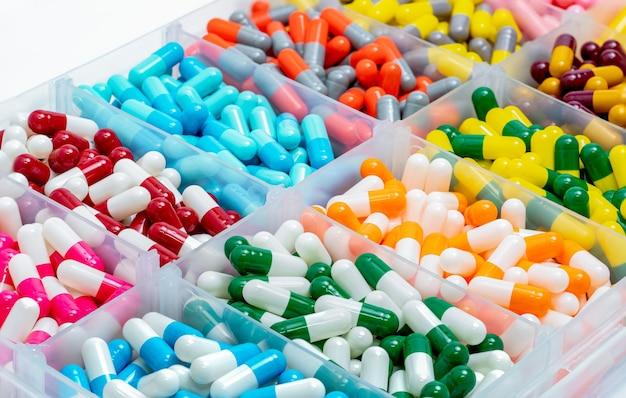 Comprimido de cápsulas coloridas em caixa de plástico.
