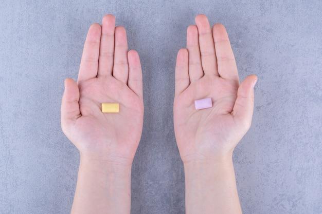 Comprimido de chiclete único em cada mão na superfície de mármore