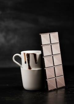 Comprimido de chocolate e chocolate derretido em canecas