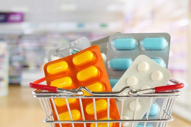 Comprimido de remédio na cesta de compras com fundo desfocado nas prateleiras das farmácias da farmácia