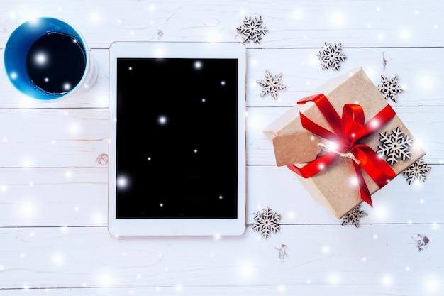 Comprimido de vista superior, xícara de café e caixa de presente com neve e flocos de neve no fundo de madeira branca para o natal e o ano novo.