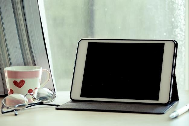 Comprimido digital na mesa no local de trabalho no fundo da janela do dia chuvoso no tom de cor vintage