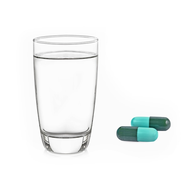 Comprimido e copo de água isolado no branco