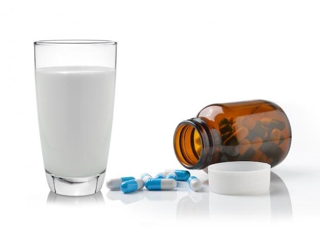 Comprimido e copo de leite, isolado no fundo branco