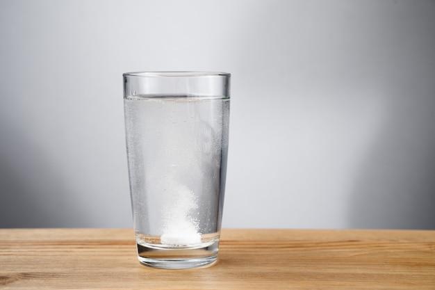 Comprimido efervescente dissolvido em um copo de água