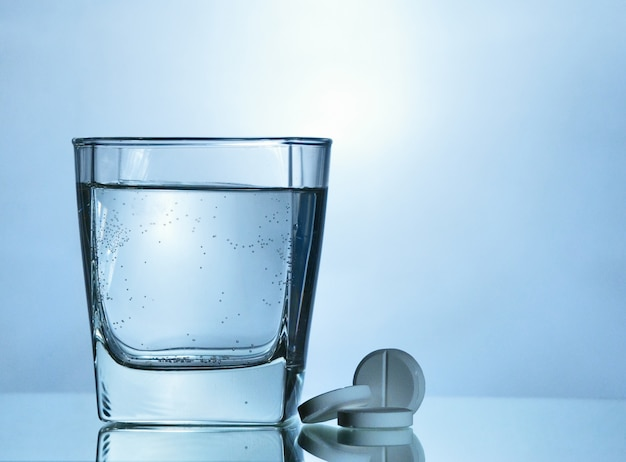 Comprimido efervescente perto de um copo com água