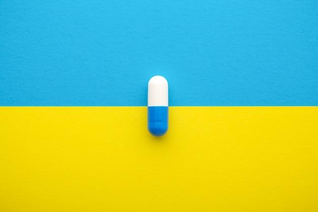 Comprimido médico em fundo amarelo azul