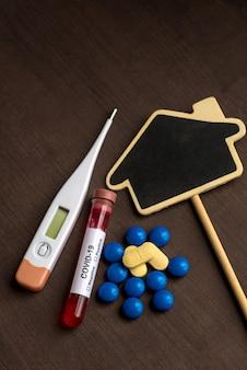 Comprimido para medicina e termômetro e quadro preto em forma de casa com tubo de ensaio contendo uma amostra de sangue para testar a presença de coronavírus