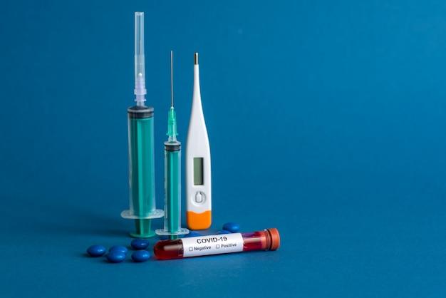 Comprimido para medicina, termômetro e seringa ou injeção com um tubo de ensaio contendo uma amostra de sangue para testar a presença de coronavírus