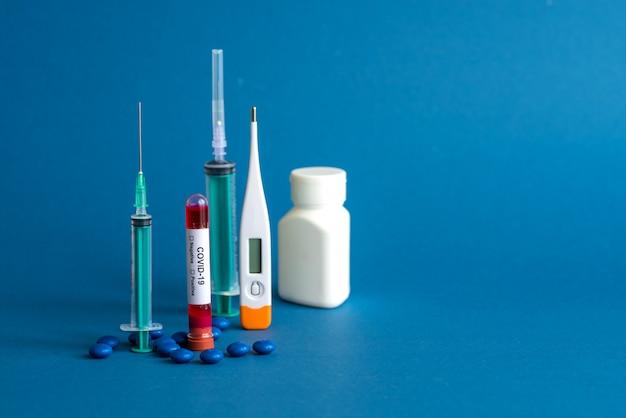 Comprimido para medicina, termômetro, frasco e seringa ou injeção com um tubo de ensaio contendo uma amostra de sangue para testar a presença de coronavírus