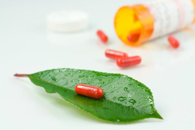 Comprimido vermelho sobre uma folha verde com um pouco de água cai sobre ele