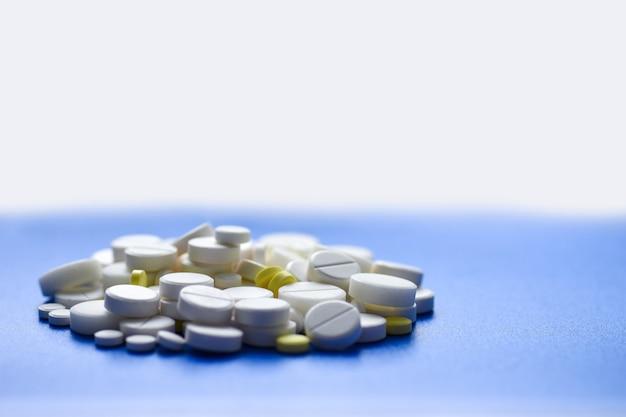 Comprimidos amarelos e brancos espalhados em uma mesa médica azul