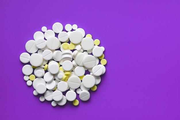 Comprimidos amarelos e brancos espalhados em uma mesa médica violeta