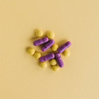 Comprimidos amarelos e cápsulas roxas no plano de fundo texturizado