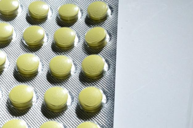 Comprimidos amarelos em uma bolha de papel alumínio mentem sobre um fundo claro. grande iplan. vista de cima