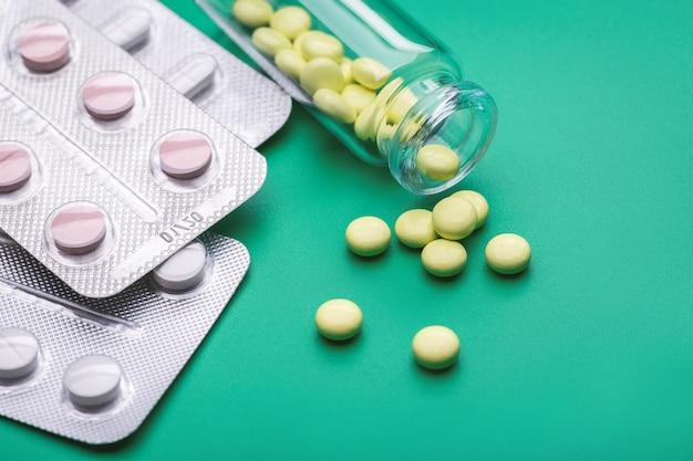 Comprimidos amarelos espalharam-se da garrafa contra um fundo verde. a embalagem blister contém diferentes comprimidos e cápsulas. indústria farmacêutica. farmacia