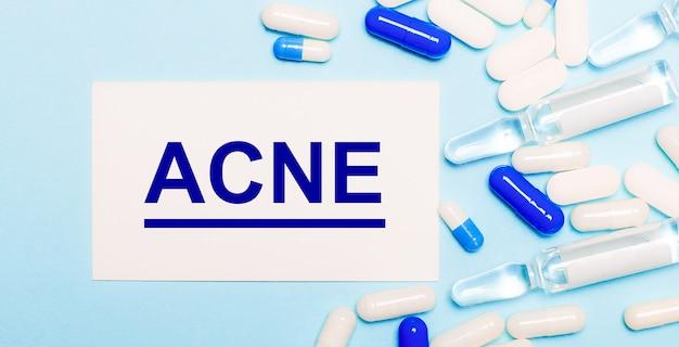 Comprimidos, ampolas e um cartão branco com o texto acne em uma superfície azul clara