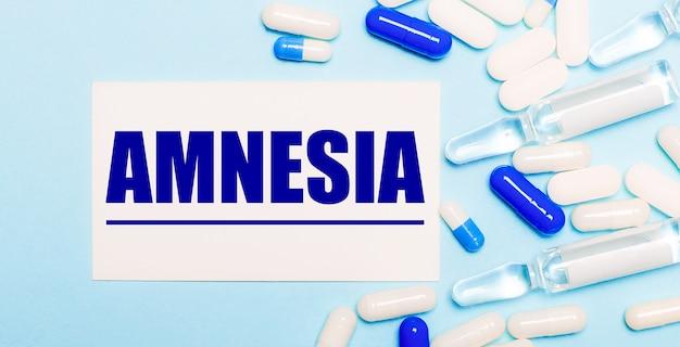 Comprimidos, ampolas e um cartão branco com o texto amnésia sobre um fundo azul claro. conceito médico