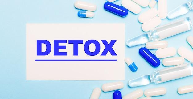 Comprimidos, ampolas e um cartão branco com o texto detox em um fundo azul claro.