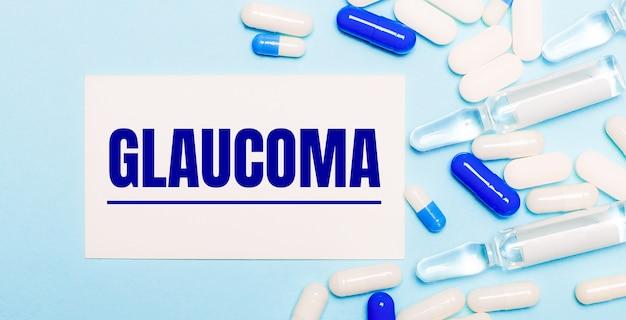 Comprimidos, ampolas e um cartão branco com o texto glaucoma em uma superfície azul clara