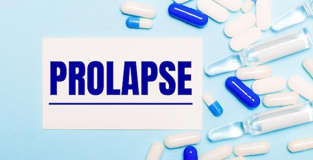 Comprimidos, ampolas e um cartão branco com o texto prolapse sobre um fundo azul claro. conceito médico.