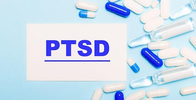 Comprimidos, ampolas e um cartão branco com o texto ptsd em uma mesa azul clara. conceito médico