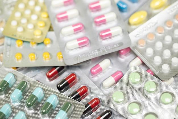 Comprimidos antibacterianos coloridos em fundo branco / medicamento em cápsula