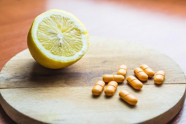 Comprimidos ao lado de um limão em uma superfície de madeira