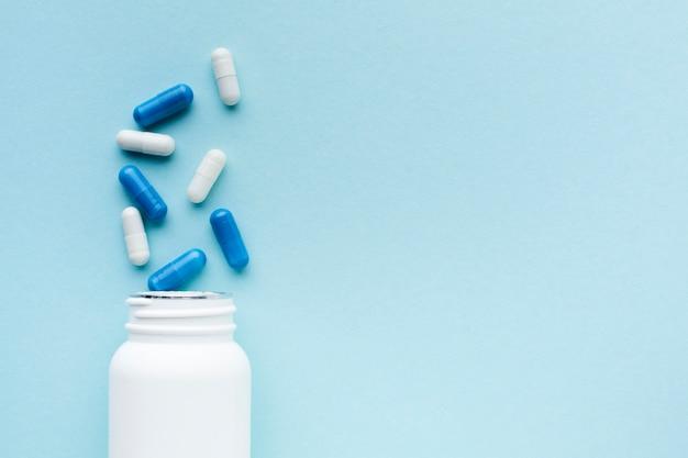 Comprimidos azuis e brancos minimalistas com garrafa de plástico