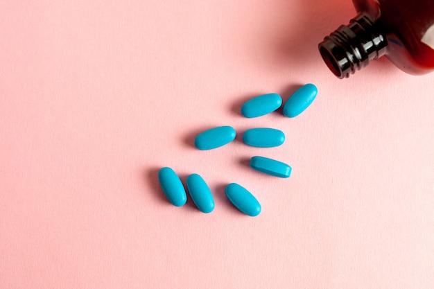 Comprimidos azuis médicos fora de uma garrafa em um fundo rosa