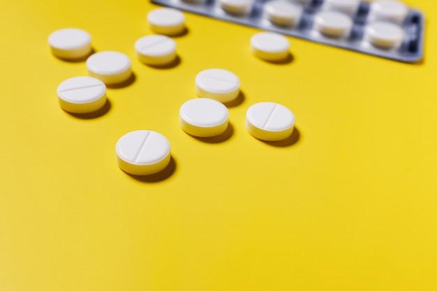 Comprimidos brancos, analgésicos na mesa amarela.
