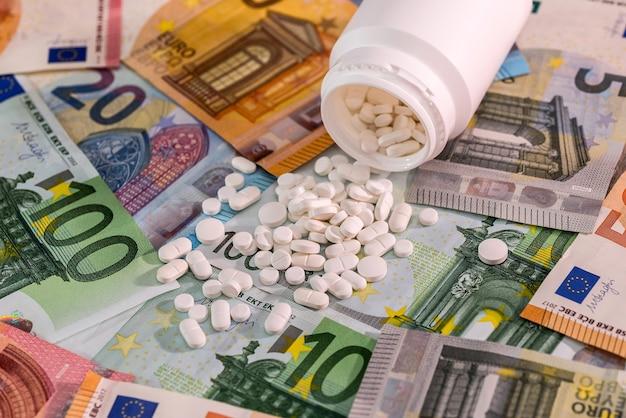 Comprimidos brancos com recipiente nas notas de euro