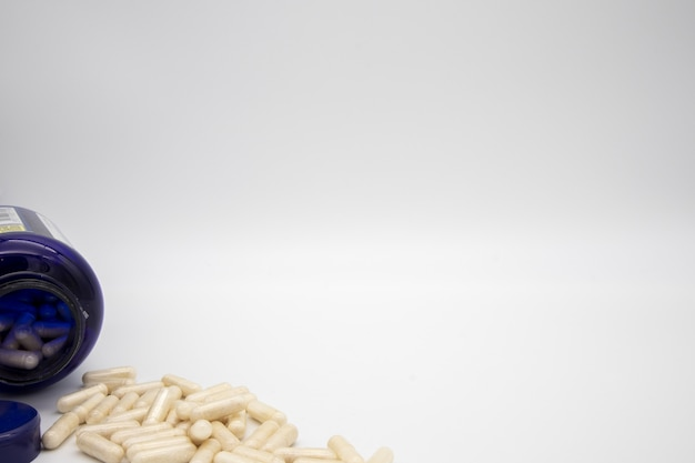 Comprimidos brancos de um frasco de comprimidos azul