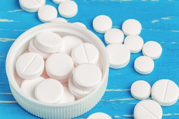 Comprimidos brancos derramado de um recipiente branco sobre azul de madeira