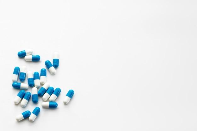 Comprimidos brancos e azuis espalhados na mesa branca.