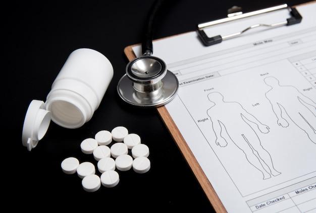 Comprimidos brancos e um frasco branco, juntamente com um estetoscópio e uma ficha médica, estão sobre um preto.