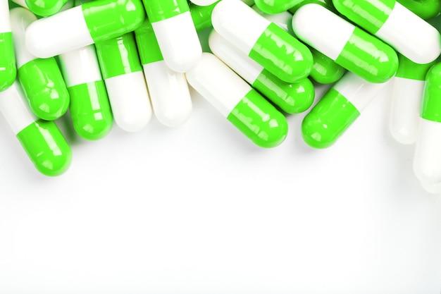Comprimidos brancos e verdes em um fundo branco. vista do topo