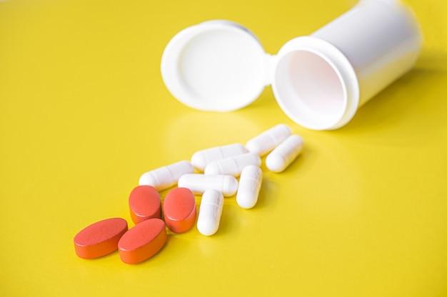 Comprimidos brancos e vermelhos são derramados de um frasco em um fundo amarelo. suplemento alimentar, multivitaminas, medicamentos. tratamento e prevenção de doenças, terapia. bem estar