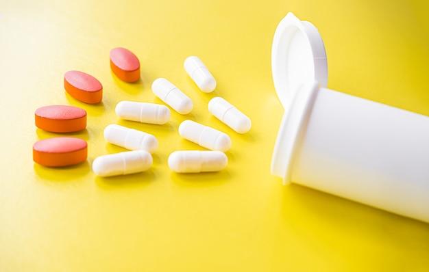 Comprimidos brancos e vermelhos são derramados de um frasco sobre um fundo amarelo. suplemento alimentar, multivitaminas, medicamentos. tratamento e prevenção de doenças, terapia. bem estar