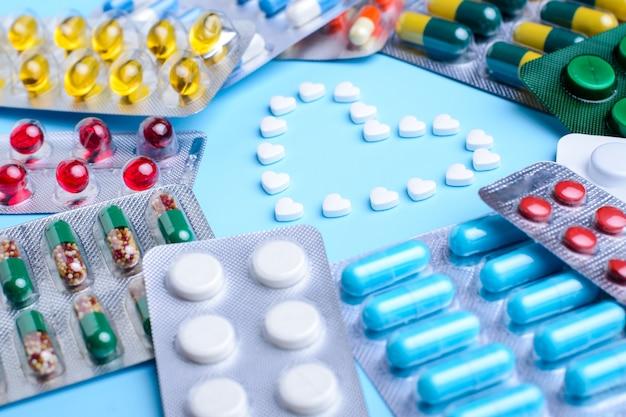 Comprimidos brancos em forma de coração, rodeados com diferentes comprimidos e cápsulas em embalagem de alumínio