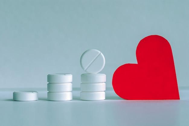 Comprimidos brancos empilhados e coração vermelho no cinza