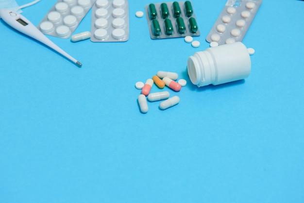 Comprimidos brancos espalhados na mesa azul. conceito de medicina, farmácia e saúde. comprimidos brancos de fundo azul com um estatoscópio médico, vista superior.